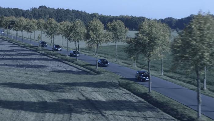 Autos fahren auf einer Landstraße umgeben von Bäumen