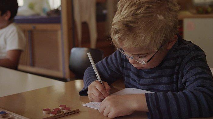 Junge sitzt am Tisch und malt